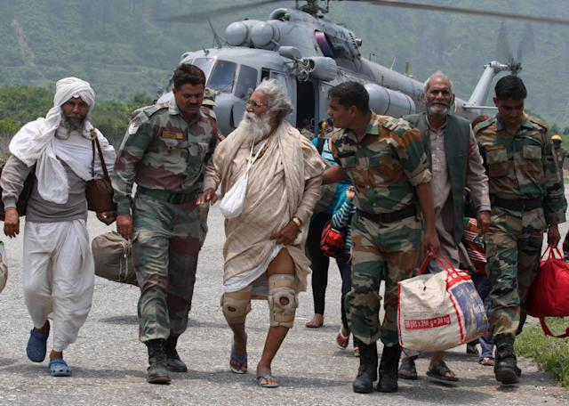 "In this handout photograph released by the Indian Ministry of Defence on June 23, 2013, Indian defence personnel assist rescued civilians from the Gangotri area after being flown to safety on board an Indian Air Force Mi-17 transport helicopter at Dharasu in Uttarakhand state on June 22, 2013. Bad weather hampered rescue operations June 23 in rain-ravaged northern India where the death toll from landslides and flash floods was likely to rise up to 1,000 with thousands of pilgrims and tourists still stranded in remote mountains without food or water for days. AFP PHOTO/MINISTRY OF DEFENCE/GURUDUTT MEHRA----EDITORS NOTE---- RESTRICTED TO EDITORIAL USE - MANDATORY CREDIT - ""AFP PHOTO/MINISTRY OF DEFENCE/GURUDUTT MEHRA"" - NO MARKETING NO ADVERTISING CAMPAIGNS - DISTRIBUTED AS A SERVICE TO CLIENTS -----"