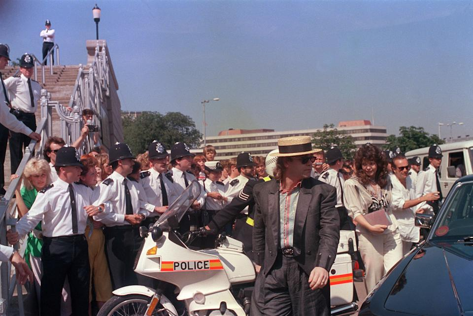 British rock star Elton John and his German wife Renate Blauel, right, walk past a police line on their arrival at Wembley Stadium, July 13, 1985, for the Live Aid concert. (AP Photo/Bob Dear)