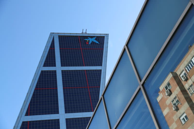 A building is reflected on glass next to CaixaBank headquarters in Madrid