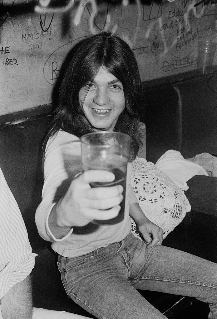 <p>AC/DC guitarist, Malcolm Young, enjoying a drink backstage after a performance at the Marquee Club. </p>
