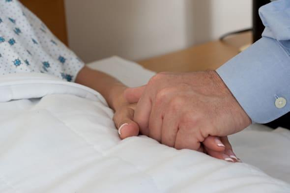 Close-up of couple holding hands while in hospital