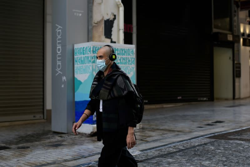 A man wearing a protective face mask makes his way on the main commercial Ermou street, amid the spread of the coronavirus disease (COVID-19), in Athens