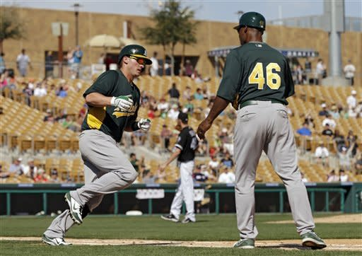 Oakland Athletics' Josh Donaldson, left, reaches out to first base coach Tye Waller (46) while rounding first after a solo home run off Chicago White Sox starting pitcher Chris Sale in the sixth inning of an exhibition spring training baseball game on Saturday, March 16, 2013, in Glendale, Ariz. (AP Photo/Mark Duncan)