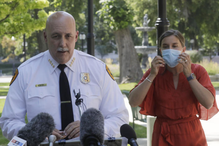 FILE - In this Aug. 3, 2020 file photo, Salt Lake City police Chief Mike Brown speaks as Mayor Erin Mendenhal listens during a news conference on Aug. 3, 2020, in Salt Lake City. The Salt Lake City Police Department vowed Tuesday, Sept. 8, 2020, to cooperate with multiple investigations of the shooting of a 13-year-old autistic boy by officers in the Salt Lake City area. The Salt Lake City Police Department said the officers were called to a home in Glendale, Utah, Friday night, Sept. 4 with a report of a boy who had threatened people with a weapon. The boy reportedly ran and was shot by an officer after being pursued by police. (AP Photo/Rick Bowmer, File)
