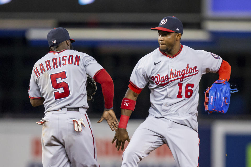 Washington Nationals center fielder Victor Robles (16) and second baseman Josh Harrison (5) celebrate a victory over the Miami Marlins in a baseball game, Thursday, June 24, 2021, in Miami. (AP Photo/Mary Holt)