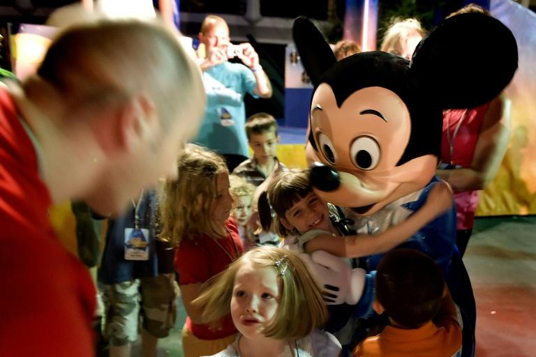 A visitor hugs Mickey Mouse at Disney World in Florida, which is set to reopen in July 2020 after a three-month closure due to the coronavirus pandemic