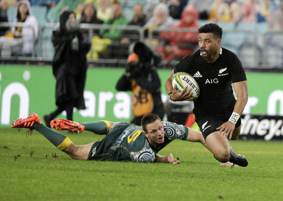 New Zealand's Richie Mo'unga falls as he looks for support as Australia's Dane Haylett-Petty, left, watches during the Bledisloe rugby test between the All Blacks and the Wallabies at Stadium Australia, Sydney, Australia, Saturday, Oct. 31, 2020. (AP Photo/Rick Rycroft)