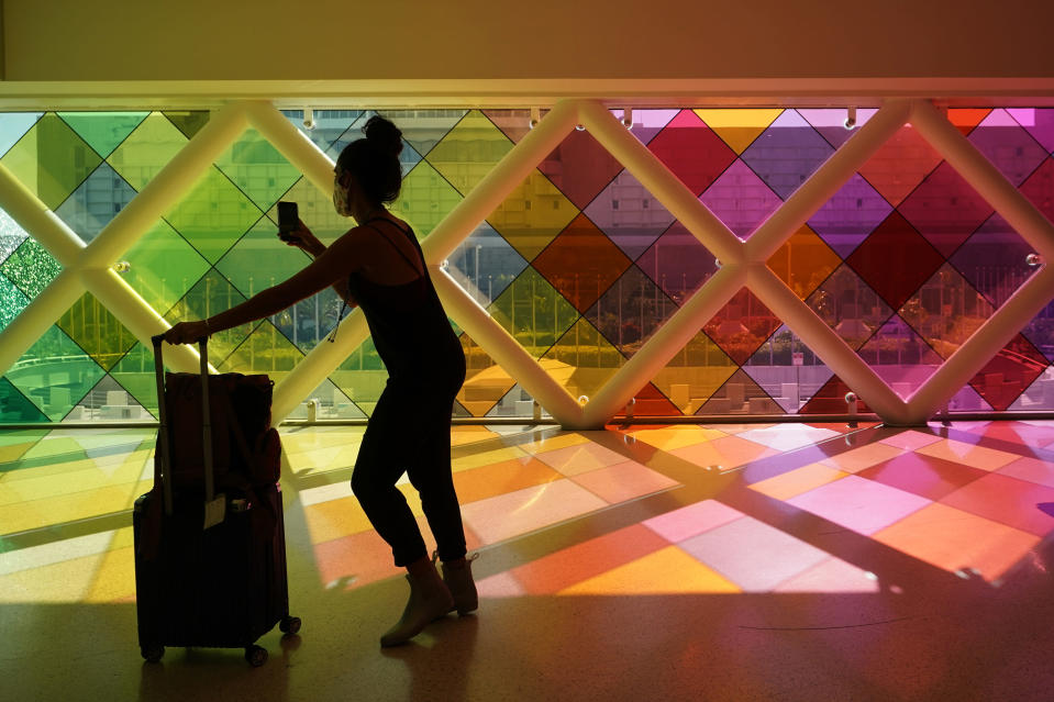 """A traveller takes photos of windows titled """"Harmonic Convergence,"""" by artist Christopher Janney, Friday, May 28, 2021, at Miami International Airport in Miami. The Greater Miami Convention and Visitors Bureau is anticipating hotel occupancy levels to surge above pre-pandemic levels. (AP Photo/Wilfredo Lee)"""