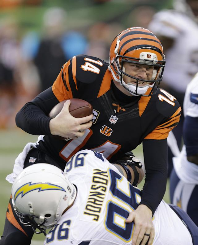 Cincinnati Bengals quarterback Andy Dalton (14) is tackled by San Diego Chargers linebacker Jarret Johnson in the second half of an NFL wild-card playoff football game on Sunday, Jan. 5, 2014, in Cincinnati. (AP Photo/Al Behrman)