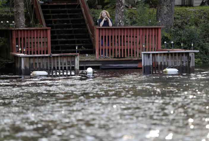 A resident stands on her pier looking out onto the rising Waccamaw River in Conway, S.C., Monday, Sept. 17, 2018. Residents are evacuating as the river is expected to flood in the coming days due heavy rains from Hurricane Florence. (AP Photo/Gerald Herbert)
