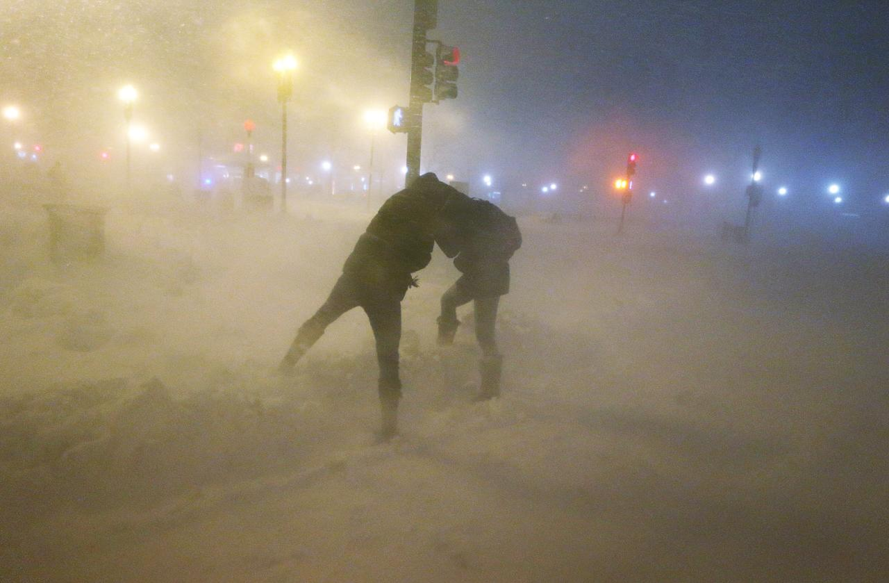 BOSTON, MA - FEBRUARY 08:  People shield themselves from the blowing snow as a blizzard arrives in the Back Bay neighborhood on February 8, 2013 in Boston, Massachusetts. Massachusetts and other states from New York to Maine are hunkered down for the major blizzard with possible record amounts of snowfall in some areas.  (Photo by Mario Tama/Getty Images)