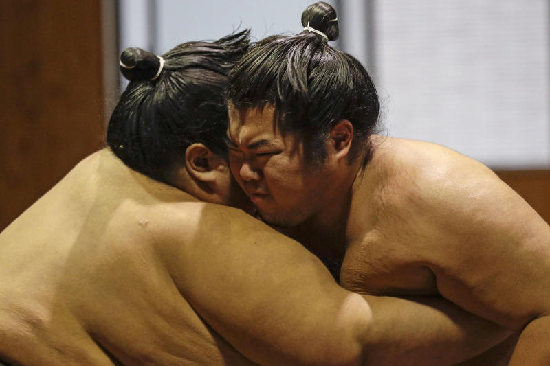 FILE - In this Oct. 18, 2019, file photo, sumo wrestlers push during training at the Musashigawa Sumo Stable at Beppu, Japan. Sumo wrestling is going to get some extra attention because of the Tokyo Olympics. The Japan Sumo Association and local Olympic organizers are planning a sumo tournament on Aug. 12-13, just days after the Olympics end. (AP Photo/Aaron Favila, File)