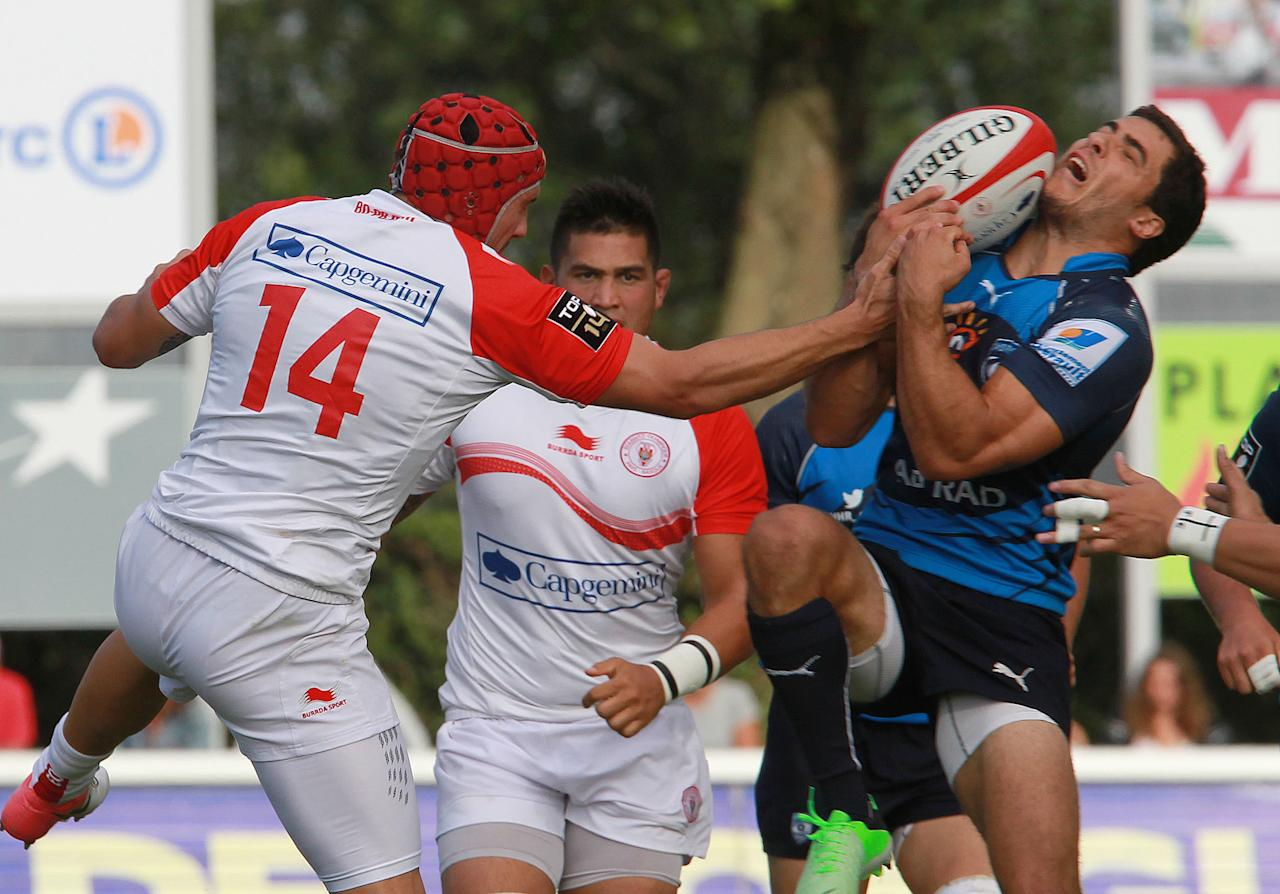Biarritz's Julen Goia, left, vies for the ball with Montpellier's Kelian Galletier, right, during their French Top 14 rugby union match at the Stade Aguilera, in Biarritz, southwestern France, Saturday Aug. 24, 2013. (AP Photo/Bob Edme)