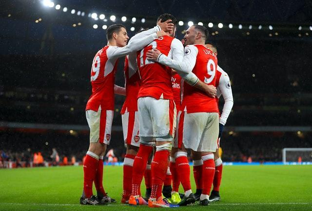 Grioud is mobbed by his Arsenal team-mates following his first-half goal at the Emirates