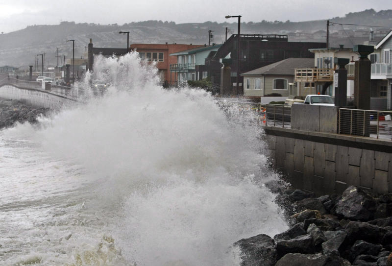 File - In this Jan. 20, 2010 file photo, waves pound a wall near buildings in Pacifica, Calif., during a rain storm. A new federal report gives the West Coast its best look yet at what to expect from rising sea levels due to climate change. The report issued by the National Research Council on Friday, June 22, 2012 says Southern and central California can expect sea levels to rise in a range of about three feel over the next century, while Northern California, Oregon and Washington can expect the range to be less _ around two feet. (AP Photo/Paul Sakuma, File)