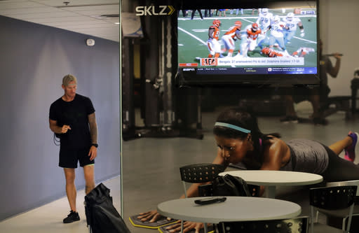 In this Oct. 8, 2018, photo, former NFL football player Nick McDonald walks down a hallway as highlights from NFL games are played on a screen at Exos in Carlsbad, Calif. McDonald played for the Green Bay Packers, New England Patriots, San Diego Chargers, and Cleveland Browns during his time playing football in the NFL. (AP Photo/Gregory Bull)