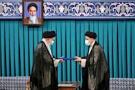 Ultraconservative Ebrahim Raisi (R) is inaugurated as president of Iran in a ceremony at the office of supreme leader Ayatollah Ali Khamenei (L)