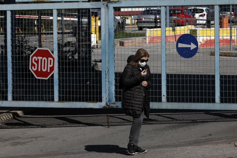 A woman wearing a face mask walks in front of Attiko Hospital in Athens, Saturday, Feb. 29, 2020. Greek Health Ministry said all carnival events in Greece would be suspended as a precautionary measure. (AP Photo/Yorgos Karahalis)