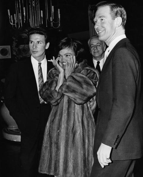 <p>Kitt and her husband Bill McDonald (at right) arrive at a party with Kitt dressed in a mink coat and her hair in a feathered sweep. </p>