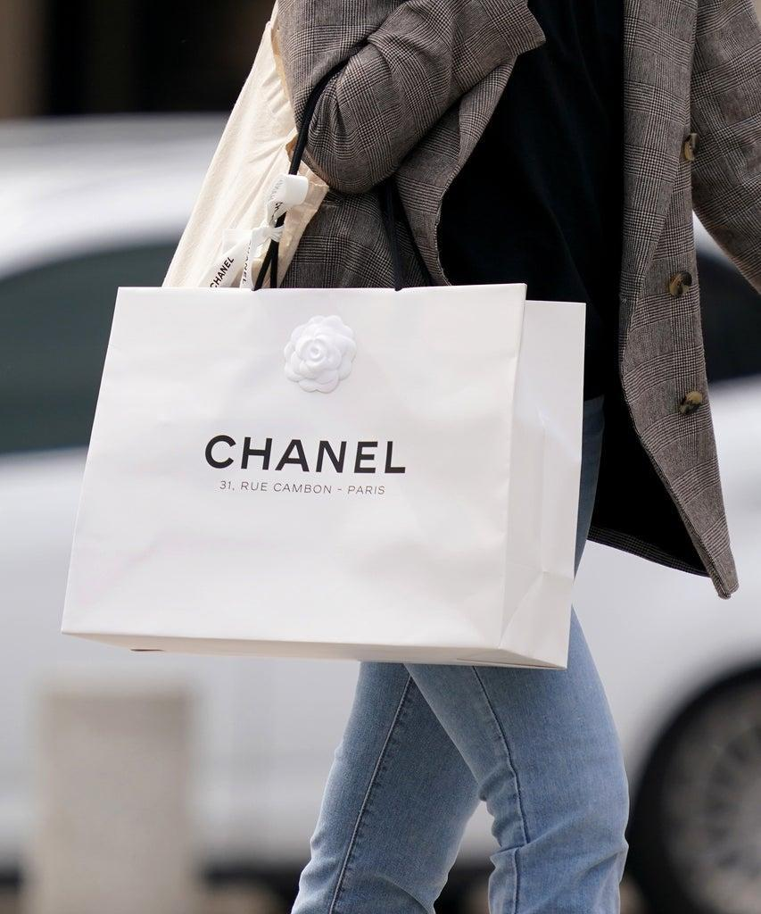 PARIS, FRANCE – MAY 11: A passerby wears a gray jacket and holds a white Chanel shopping bag, in the streets of Paris, on May 11, 2020 in Paris, France. (Photo by Edward Berthelot/Getty Images)