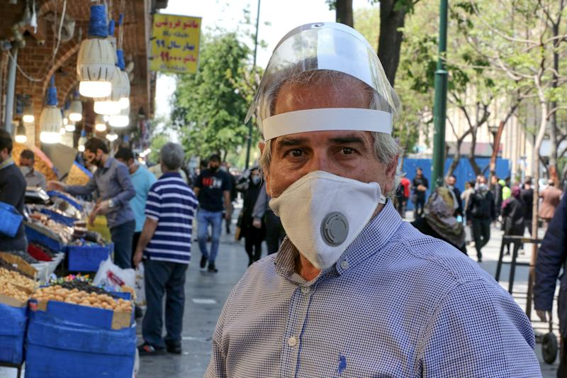 An Iranian man, wearing personal protective equipment amid the COVID-19 pandemic, shops at the Grand Bazaar market in the capital Tehran, on April 18, 2020. - Iran allowed some shuttered Tehran businesses to reopen on April 18 despite the Middle East's deadliest coronavirus outbreak, as many faced a bitter choice between risking infection and economic ruin. (Photo by ATTA KENARE / AFP) (Photo by ATTA KENARE/AFP via Getty Images)