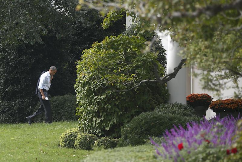 """President Barack Obama walks back to the Oval Office after he visited Martha's Table, which assists the poor and where furloughed federal employees are volunteering, in Washington, Monday, Oct. 14, 2013. Speaking there Obama said that if Republicans can't resolve the standoff over the debt ceiling and the partial government shutdown, quote, """"we stand a good chance of defaulting."""" (AP Photo/Charles Dharapak)"""