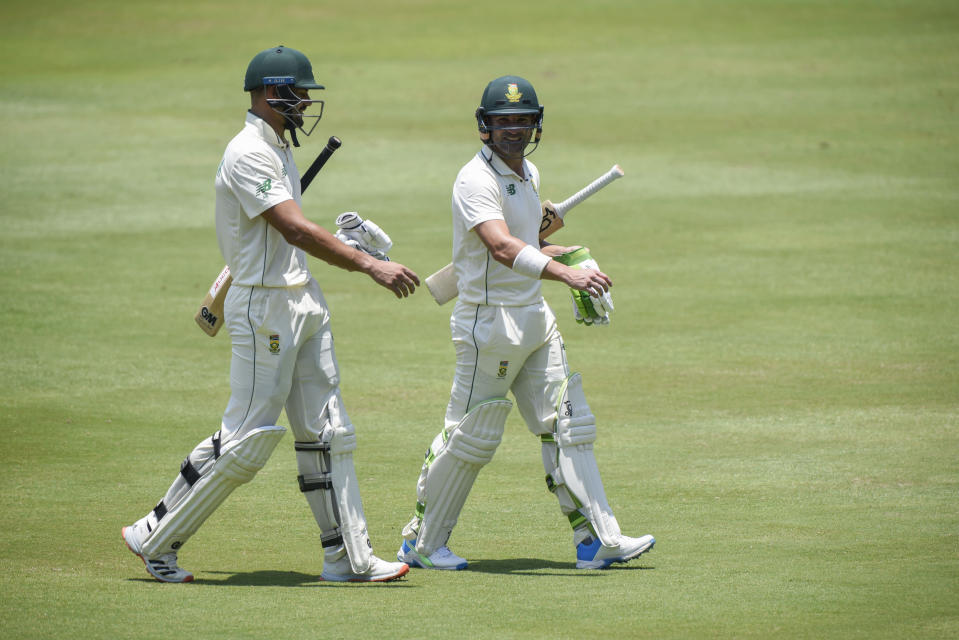 South Africa's Aiden Markram left, and South Africa's Dean Elgar right, leave the playing field for lunch during South Africa first innings, on day two of the first cricket test match between South Africa and Sri Lanka at Super Sport Park Stadium in Pretoria, South Africa, Sunday, Dec. 27, 2020. (AP Photo/Catherine Kotze)