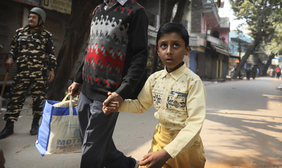 A child looks at an Indian paramilitary soldier standing guard after Tuesday's violence in New Delhi, India, Wednesday, Feb. 26, 2020. At least 20 people were killed in three days of clashes in New Delhi, with the death toll expected to rise as hospitals were overflowed with dozens of injured people, authorities said Wednesday. The clashes between Hindu mobs and Muslims protesting a contentious new citizenship law that fast-tracks naturalization for foreign-born religious minorities of all major faiths in South Asia except Islam escalated Tuesday. (AP Photo/Manish Swarup)