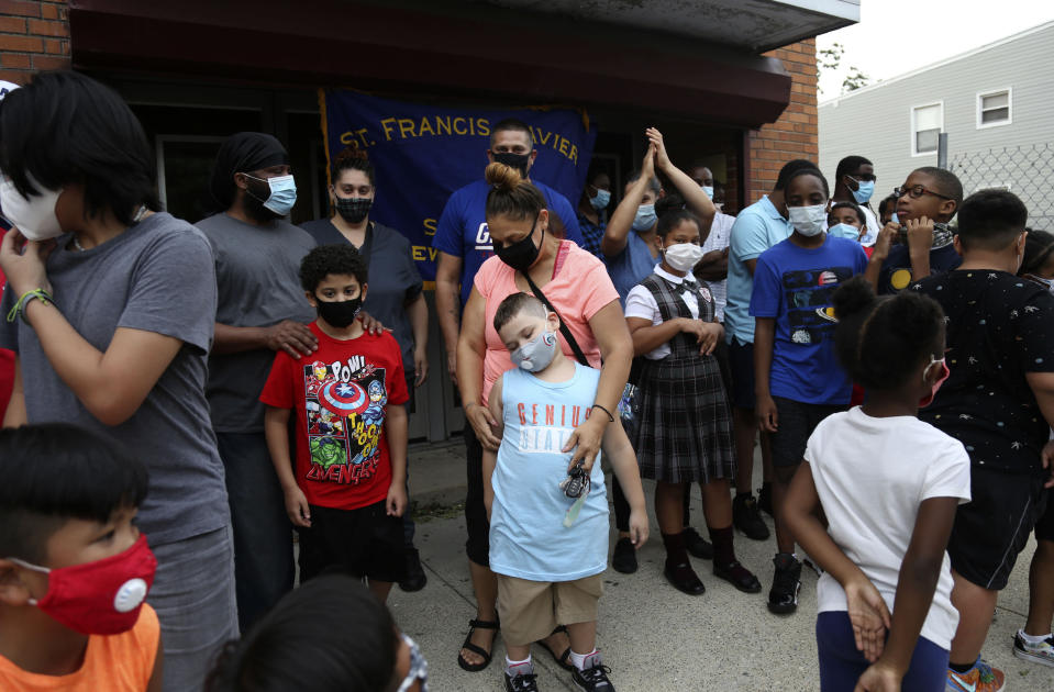 Dozens of students and their family members gather outside St. Francis Xavier School in Newark on Thursday, Aug. 6, 2020, a week after the Archdiocese of Newark announced its permanent closure. (AP Photo/Jessie Wardarski)