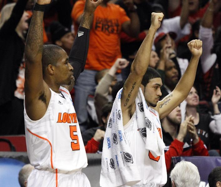 Louisville's Peyton Siva, right, and JP Kuhlman celebrate a score from the bench during the first half of their NCAA tournament second-round college basketball game against Davidson in Portland, Ore., Thursday, March 15, 2012.(AP Photo/Don Ryan)