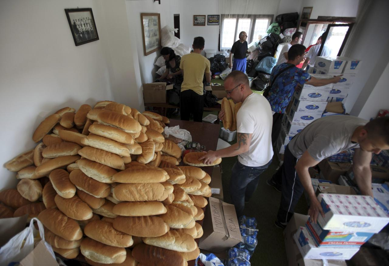 Volunteers prepare food for people affected by floods in the town of Smedarevska Palanka, southeast of Belgrade, May 20, 2014. Soldiers and energy workers stacked thousands of sandbags overnight to protect Serbia's biggest power plant from flood waters expected to keep rising after the heaviest rains in the Balkans in more than a century killed dozens of people. REUTERS/Antonio Bronic (SERBIA - Tags: DISASTER ENVIRONMENT)