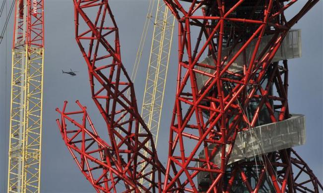 A helicopter flies near the Anish Kapoor designed ArcelorMittal Orbit tower at the Olympic site at Stratford in east London October 7, 2011.