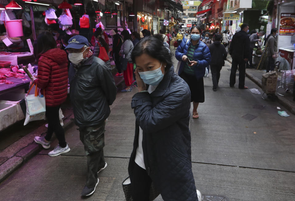 Pictured: Woman wears mask to prevent coronavirus in busy Hong Kong street. (AP Photo/Achmad Ibrahim)