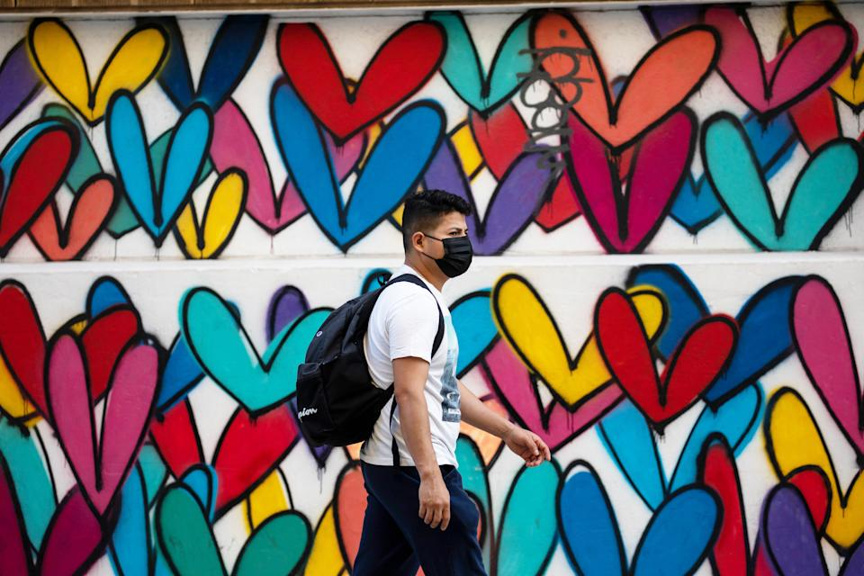 A man wearing a face mask passes a mural of heart-shaped patterns in the Brooklyn borough of New York, the United States, Oct. 2, 2021. (Michael Nagle/Xinhua via Getty Images)