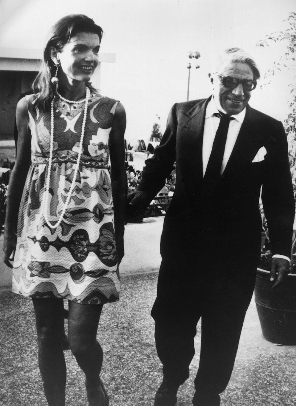 <p>Jackie and her second husband, Aristotle Onassis, leave an Athens nightclub after celebrating her 40th birthday. Jackie wears a minidress with a bold pattern, a long string of pearls, and Lalaounis earrings.<br></p>