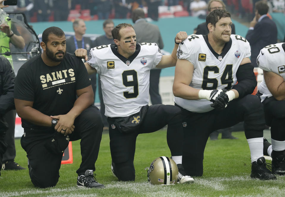 Saints quarterback Drew Brees (9) kneels down with teammates before the U.S. national anthem was played before New Orleans' game against Miami in London. (AP)