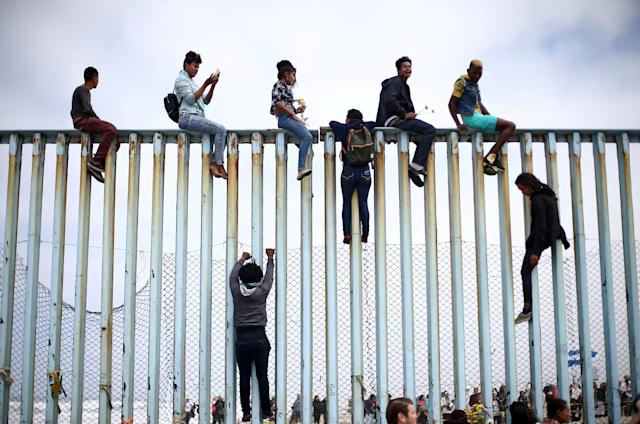Members of a caravan of migrants from Central America climb up the border fence between Mexico and the U.S., as a part of a demonstration prior to preparations for an asylum request in the U.S., in Tijuana, Mexico, April 29, 2018. REUTERS/Edgard Garrido