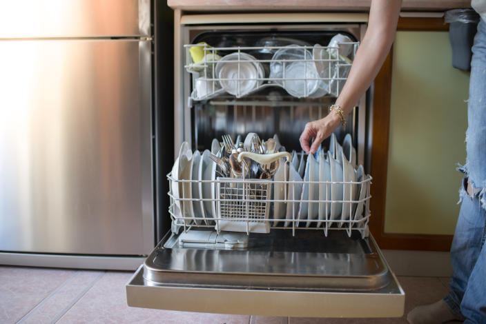 Housewife placing dishes in the dishwasher. Hand or machine dishwashing. Close up shot of modern housewife taking out clean dishes from dishwasher machine.