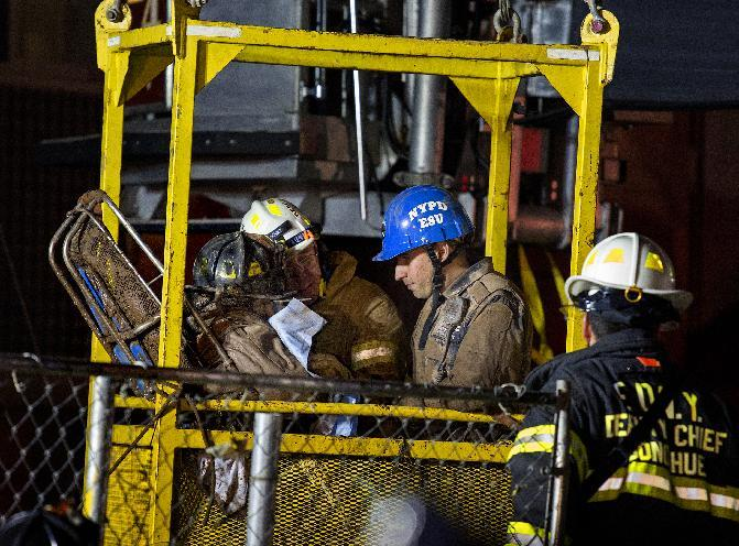 A worker, with black fire helmet at left inside a construction transport bucket, is rescued from an MTA subway construction project in New York early Wednesday, March 20, 2013 after being trapped up to his chest in debris for several hours. Fire officials say he is awake and conscious and is being evaluated at a local hospital. (AP Photo/Craig Ruttle)