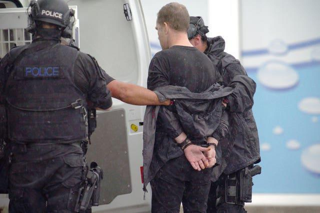 A man is led away after being arrested by police (Ben Birchall/PA)