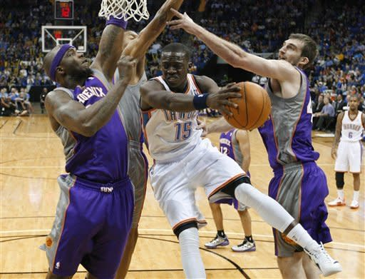Oklahoma City Thunder guard Reggie Jackson (15) looks for a teammate to pass to, between Phoenix Suns center Jermaine O'Neal, left, and forward Luke Zeller during the second quarter of an NBA preseason basketball game in Tulsa, Okla., Friday, Oct. 19, 2012. (AP Photo/Sue Ogrocki)