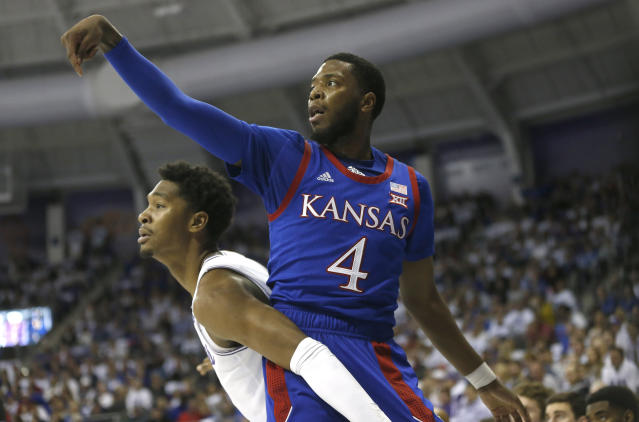 Kansas guard Isaiah Moss (4) scores on a 3-point shot as TCU forward Diante Smith (10) looks on during the first half of an NCAA college basketball game, Saturday, Feb. 8, 2020, in Fort Worth, Texas. (AP Photo/Ron Jenkins)