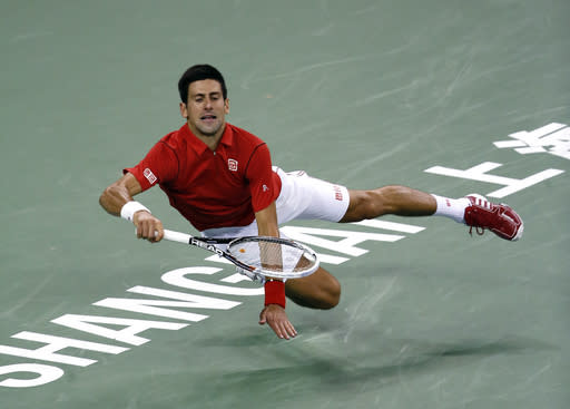 Serbia's Novak Djokovic stumbles as he returns a shot to Juan Martin del Potro of Argentina during the singles final of the Shanghai Masters tennis tournament at Qizhong Forest Sports City Tennis Center, in Shanghai, China, Sunday, Oct. 13, 2013. Djokovic won 6-1, 3-6, 7-6. (AP Photo/Eugene Hoshiko)