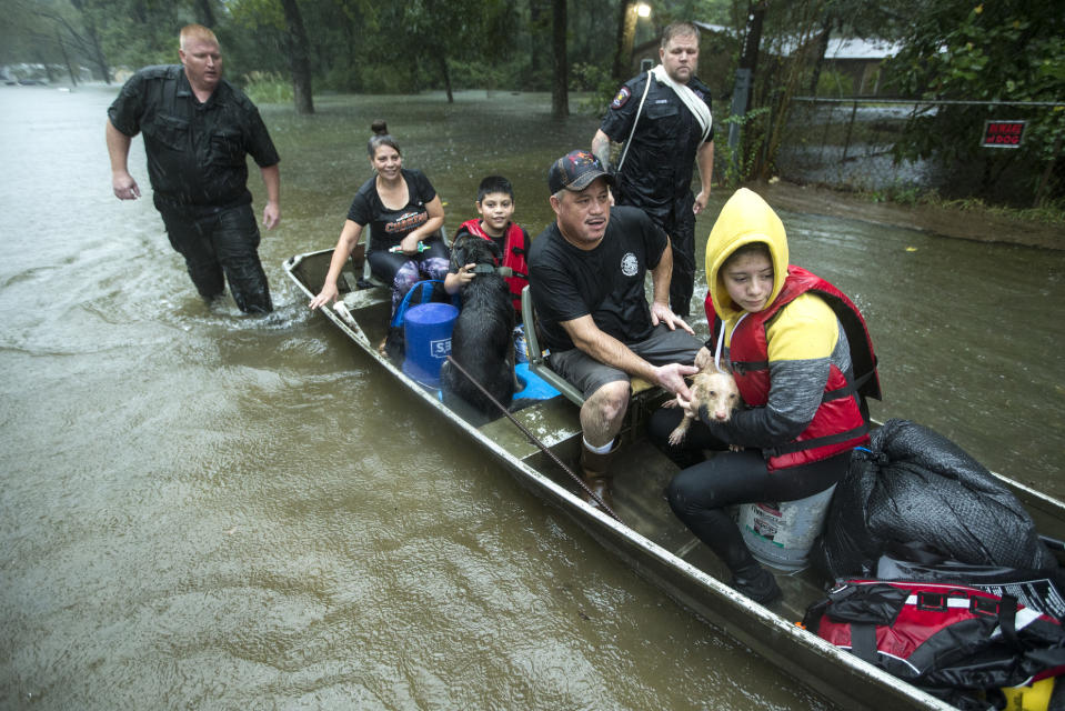 Splendora Police officers Lt. Troy Teller, left, and Cpl. Jacob Rutherford guide a boat carrying Maria, Ramiro, Jr., Ramiro and and Veronica Lopez from their flooded neighborhood inundated by rains from Tropical Depression Imelda inundates the area on Sept. 19, 2019, in Spendora, Texas. (Photo: Brett Coomer/Houston Chronicle via AP)