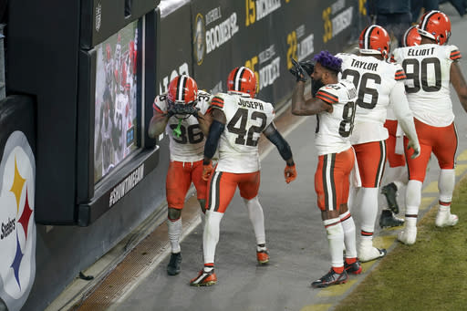 Members of the Cleveland Browns defense celebrate an interception of a pass by Pittsburgh Steelers quarterback Ben Roethlisberger during the second half of an NFL wild-card playoff football game, late Sunday, Jan. 10, 2021, in Pittsburgh. The Browns won 48-35. (AP Photo/Keith Srakocic)