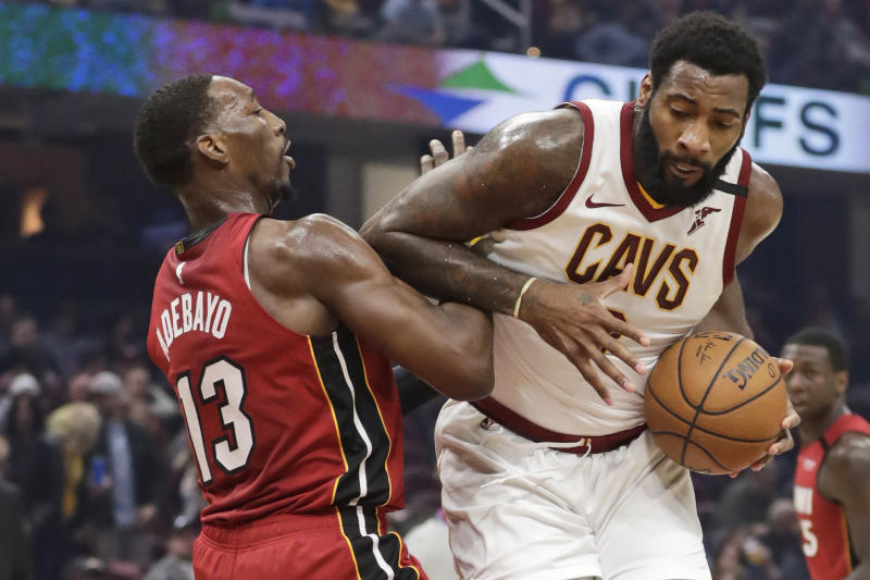 FILE - Cleveland Cavaliers' Andre Drummond, right, drives past Miami Heat's Bam Adebayo in the first half of an NBA basketball game,  in Cleveland.  On Friday, March 6, Drummond, Cavs guards Collin Sexton and Darius Garland, forwards Cedi Osman, Dante Exum and Dylan Windler, coach J.B. Bickerstaff, his entire staff and general manager Koby Altman, spent several hours visiting with offenders at Grafton _ a medium security prison housing 1,700 residents to share fellowship as well as some hope and hoops.(AP Photo/Tony Dejak)