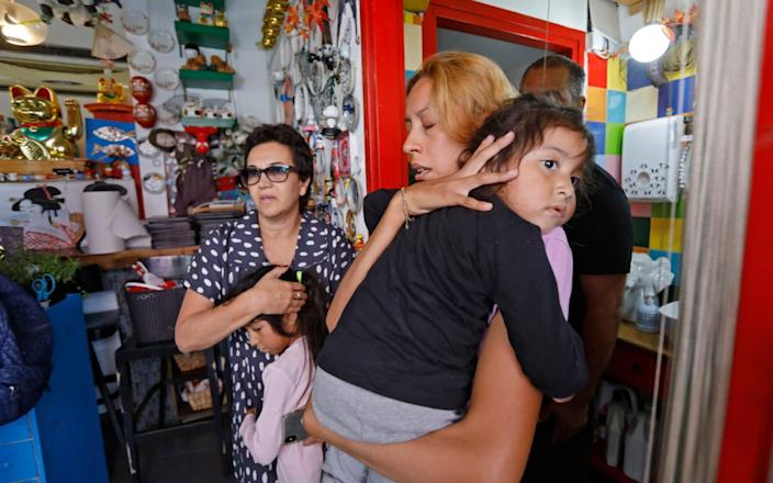 Israelis take cover in a shop as a siren rings during an attack of rockets from Gaza, in the country's Mediterranean city of Bat Yam, south of Tel Aviv. - AFP