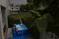 "A group of young girls enjoy themselves in a portable plastic pool on a private patio in Seville, Spain on Aug. 11, 2020. Elena Tapia, the owner said that ""I bought the pool because of the Covid-19. The great thing to have it is that as the owner I don't have to keep any schedule and during the heat wave I can swim whenever I want"". (AP Photo/ Laura Leon)"
