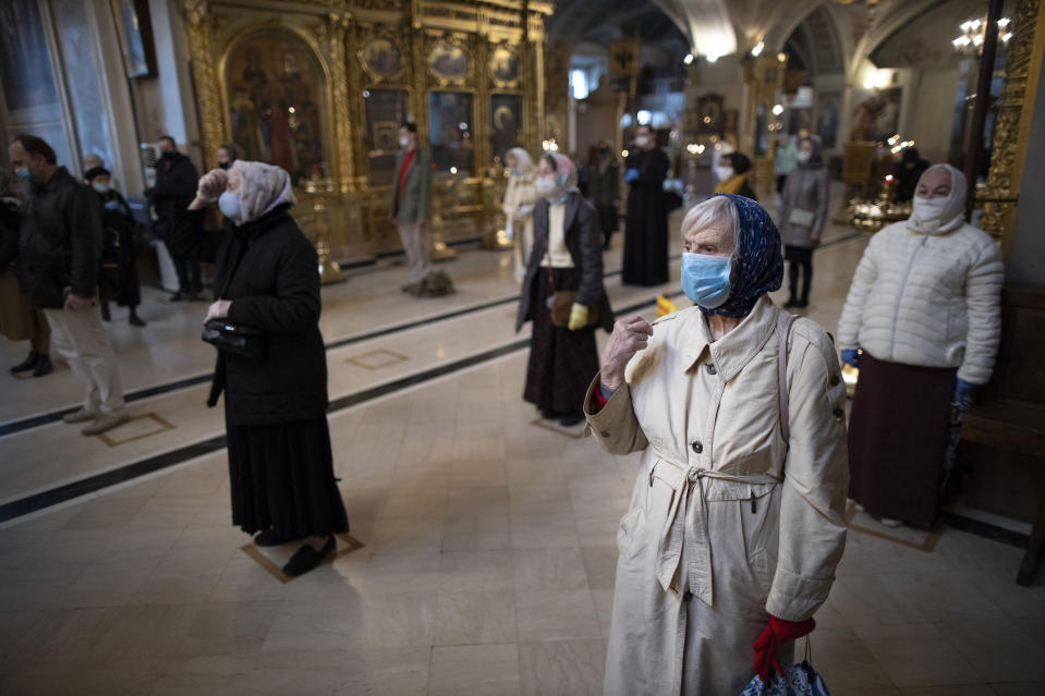 Parishioners wearing face masks to protect against coronavirus, observe social distancing guidelines cross themselves as they attend service at the Epiphany Cathedral in Moscow, Russia, Tuesday, June 2, 2020. Churches in Moscow reopen to believers after a two-month lockdown imposed to control the spread of the coronavirus. (AP Photo/Alexander Zemlianichenko)