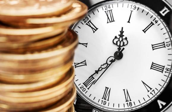 A stack of coins in front of a clock.